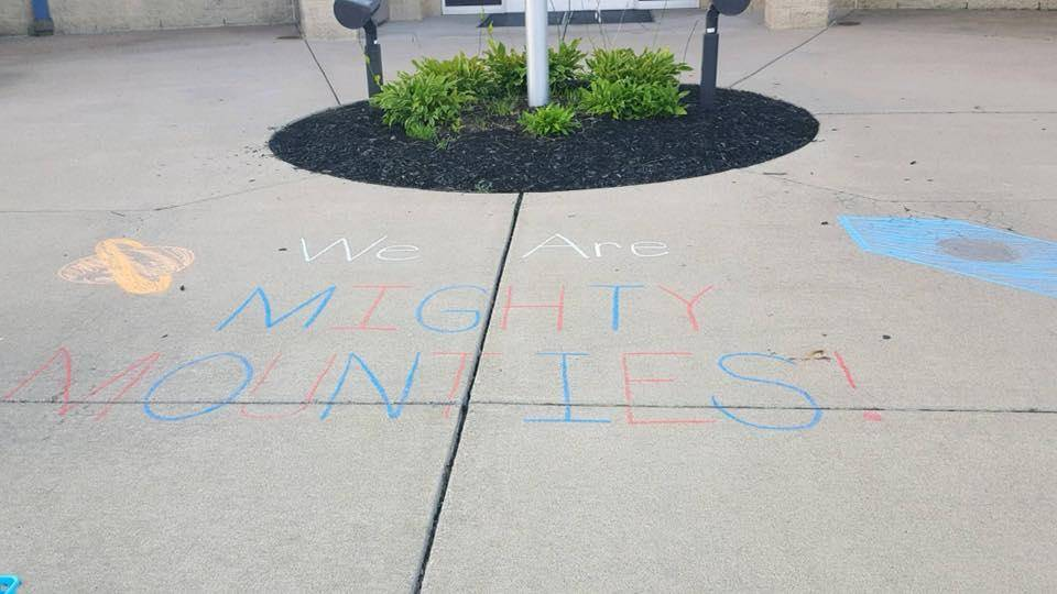 """We Are Mighty Mounties"" written in chalk on the ground"
